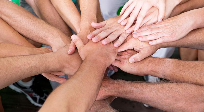 Hände von verschiedenen Menschen übereinander