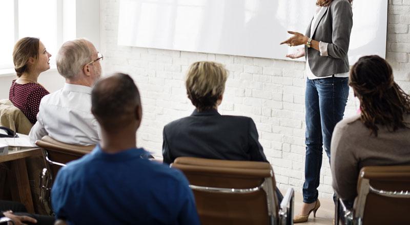 Eine Frau hält einen Vortrag vor sitzenden Menschen