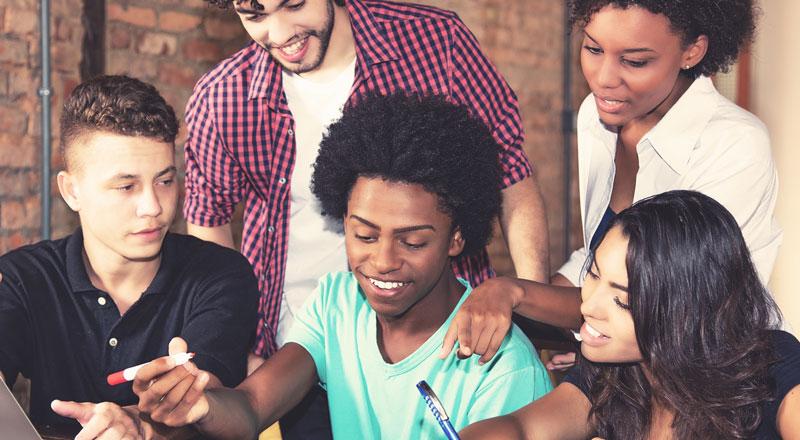 Junge Menschen machen eine gemeinsame Aufgabe mit Malstifte