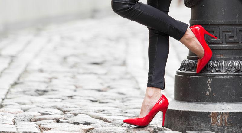 Beine einer Frau, stehend an einer Laterne